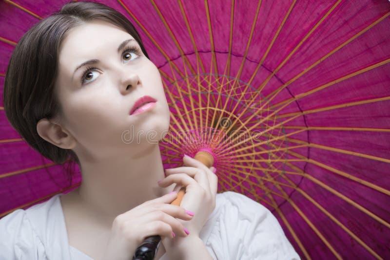 De jonge vrouw onder houten purple oriënteert paraplu royalty-vrije stock foto's