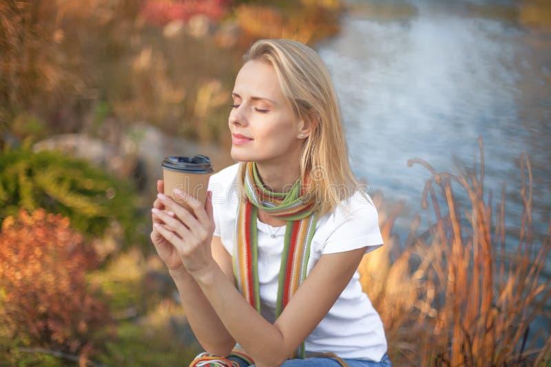 De jonge vrouw ontspant en genietend van drinkend koffie op de natuurlijke achtergrond van de ochtend verse lucht stock foto