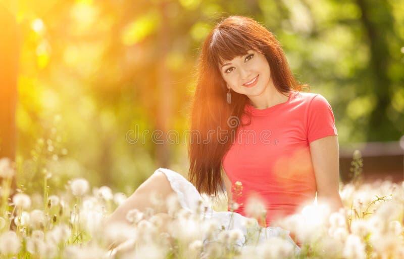 De jonge vrouw ontspant in het park met bloemen De sc?ne van de schoonheidsaard met kleurrijke achtergrond, bomen en bloemen bij  royalty-vrije stock foto's