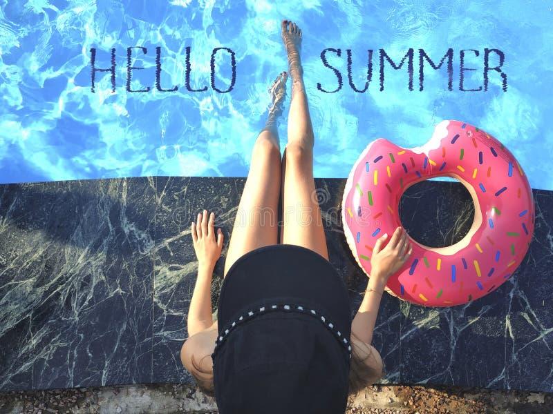 De jonge vrouw ontspant met doughnut in het zwembad bij kuuroordtoevlucht Mening van hierboven stock fotografie