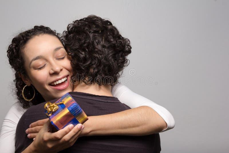 De jonge vrouw ontvangt aanwezige Kerstmis Het gelukkige meisje koestert hij royalty-vrije stock fotografie