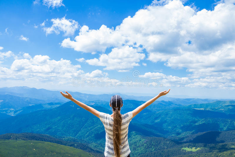 De jonge vrouw op de piek van de berg heft op hand op en geniet van mooie mening van hemel en bergen Verschillende 3d bal royalty-vrije stock foto