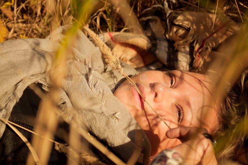 De jonge vrouw is op het dalingsgras stock foto