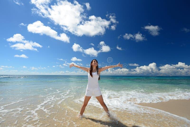De jonge vrouw op het strand geniet van zonlicht royalty-vrije stock foto's