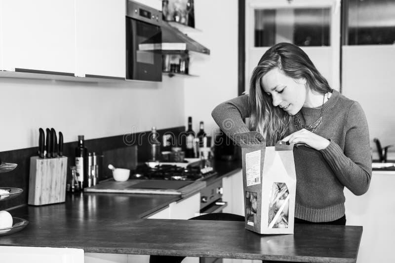 De jonge vrouw opent een pakket van verse ingrediënten stock afbeeldingen