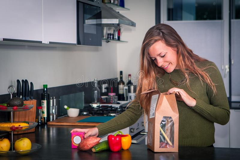 De jonge vrouw opent een pakket van verse ingrediënten om een gezond diner te maken royalty-vrije stock foto's