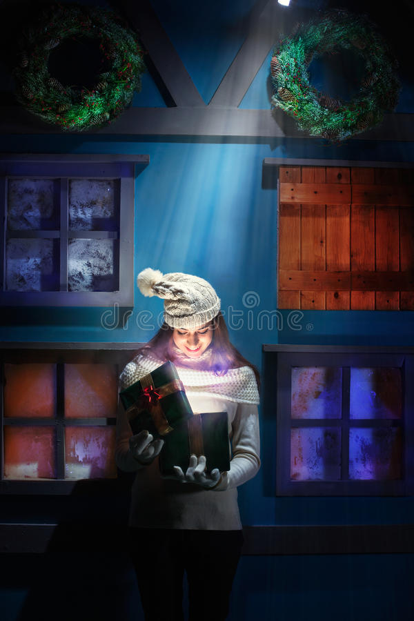 De jonge vrouw opent haar giftkerstmis in een magisch huis stock afbeeldingen