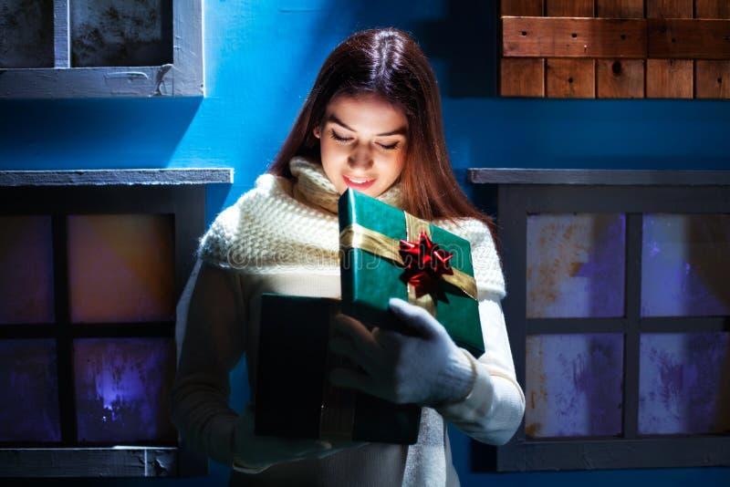 De jonge vrouw opent haar giftkerstmis in een magisch huis royalty-vrije stock foto's
