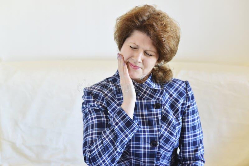 De jonge vrouw in pijn heeft een tandpijn stock foto's