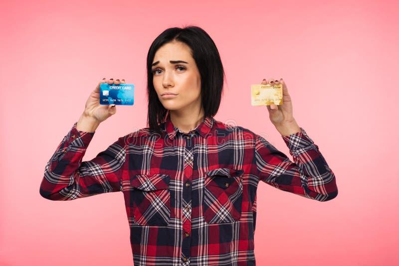 De jonge vrouw in rood plaidoverhemd toont twee creditcards op roze achtergrond royalty-vrije stock foto's