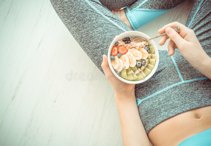 De jonge vrouw rust en eet een gezond havermeel na een training stock foto's