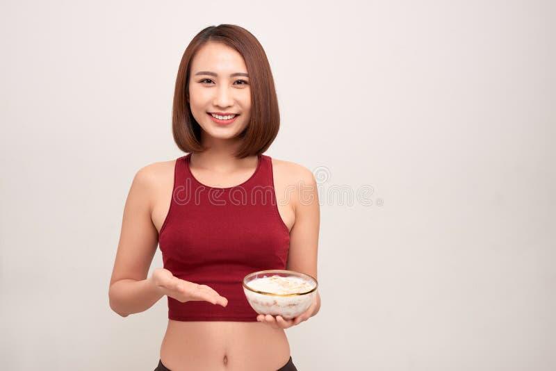 De jonge vrouw rust en eet een gezond havermeel na een training stock afbeelding