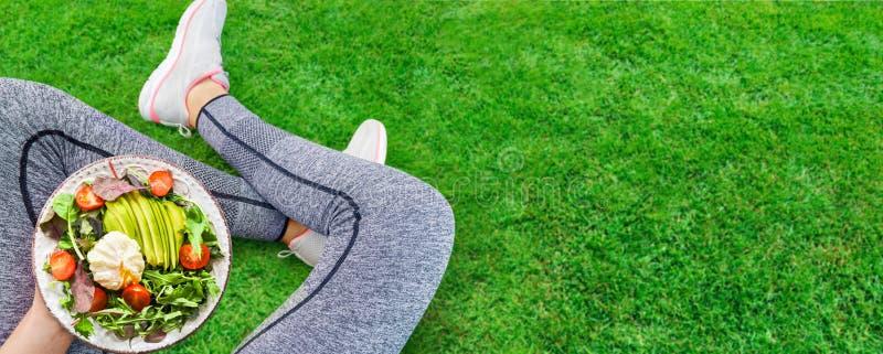 De jonge vrouw rust en eet een gezond voedsel na een training stock afbeelding