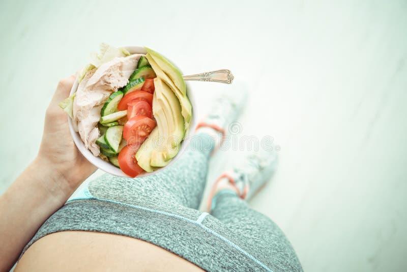De jonge vrouw rust en eet een gezonde salade na een training royalty-vrije stock foto's