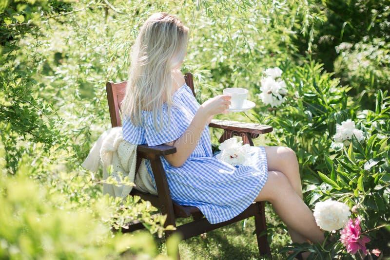 De jonge vrouw rust in de tuin op een stoel met een kop van te royalty-vrije stock afbeeldingen