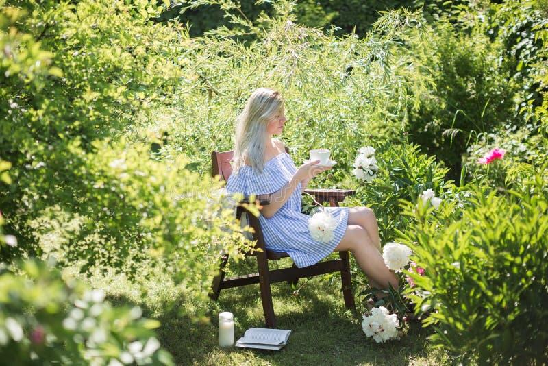 De jonge vrouw rust in de tuin op een stoel met een kop van te stock fotografie