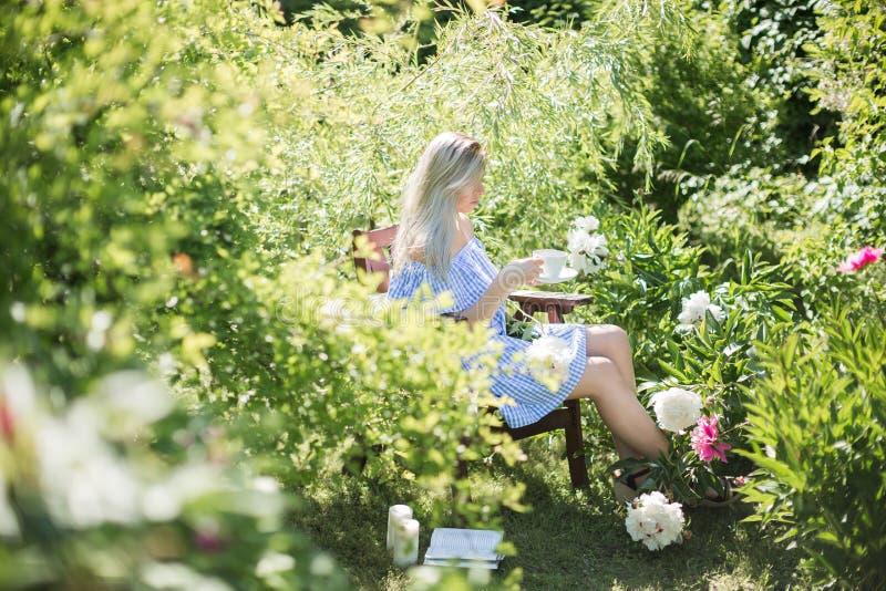 De jonge vrouw rust in de tuin op een stoel met een kop van te stock foto's