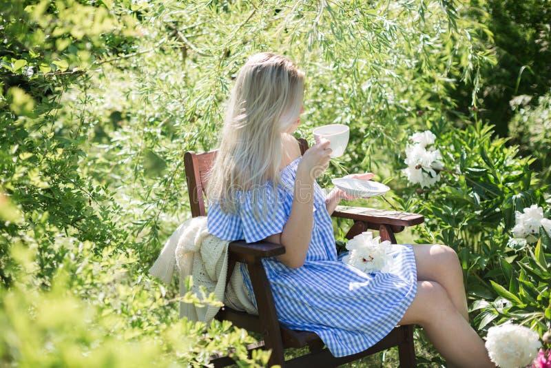 De jonge vrouw rust in de tuin op een stoel met een kop van te stock afbeeldingen