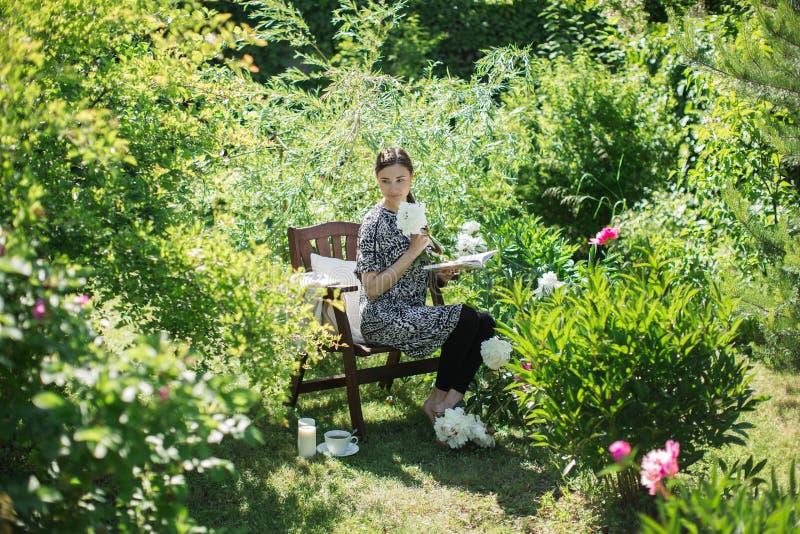 De jonge vrouw rust in de tuin op een stoel met een kop van te royalty-vrije stock foto
