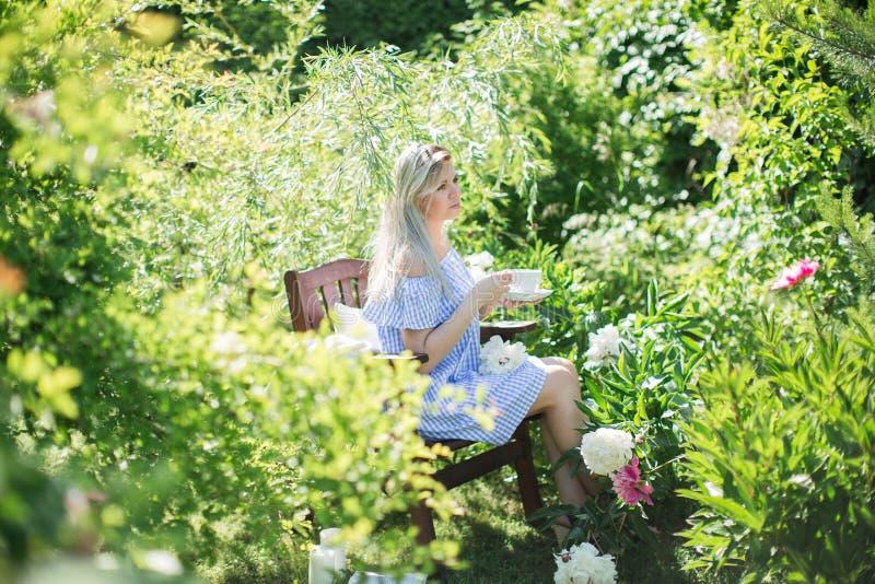 De jonge vrouw rust in de tuin op een stoel met een kop van te royalty-vrije stock fotografie