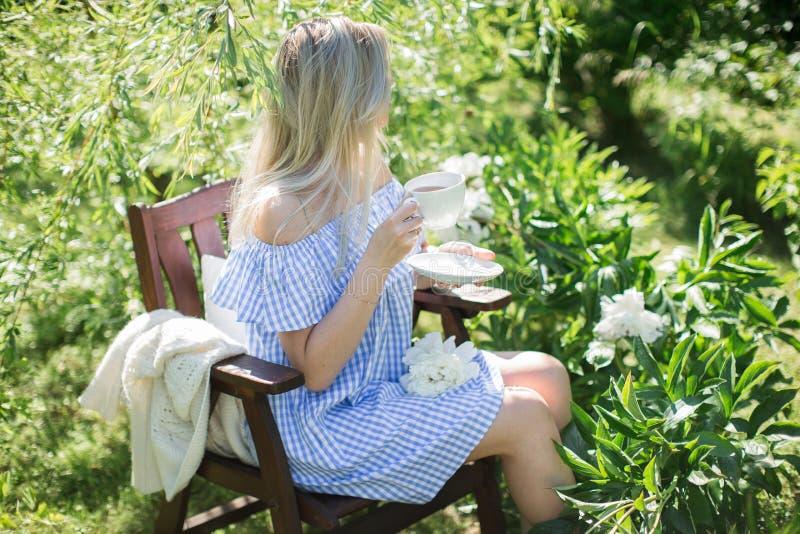 De jonge vrouw rust in de tuin op een stoel met een kop van te royalty-vrije stock afbeelding