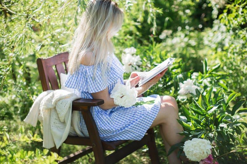 De jonge vrouw rust in de tuin op een stoel met een kop van te stock foto