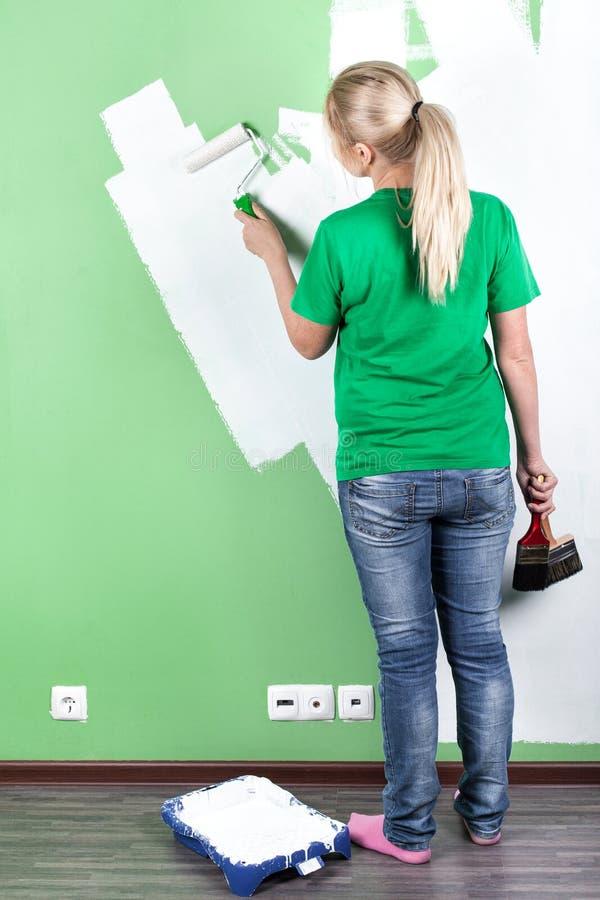 De jonge vrouw schildert de muur royalty-vrije stock foto