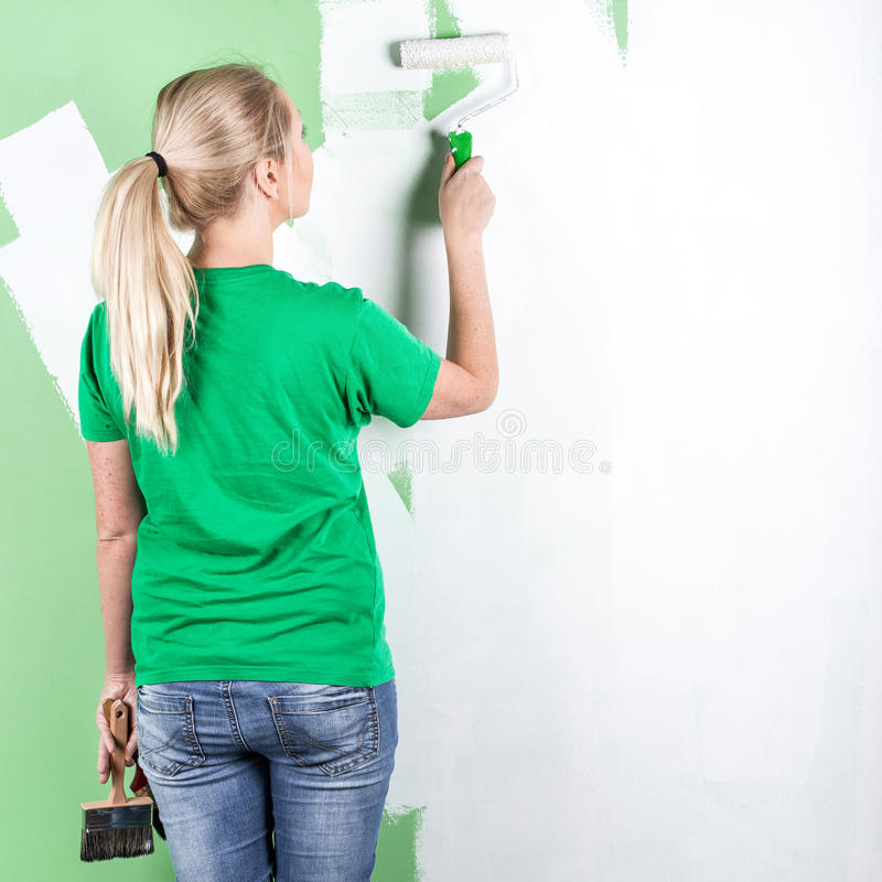 De jonge vrouw schildert de muur royalty-vrije stock afbeeldingen