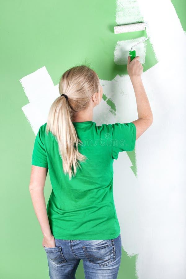 De jonge vrouw schildert de muur stock fotografie