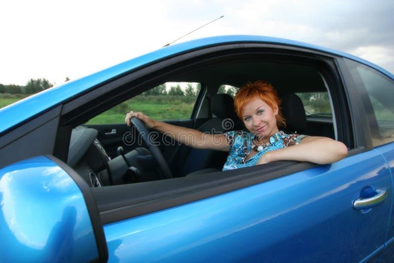 De jonge vrouw situeert in een auto stock afbeelding