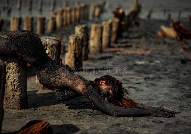 De jonge vrouw smeerde met therapeutische modder en ligt op houten colu stock foto's