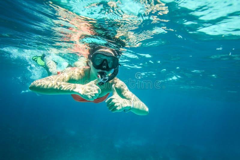 De jonge vrouw snorkelt, tegenhoudend twee duimen stock foto's