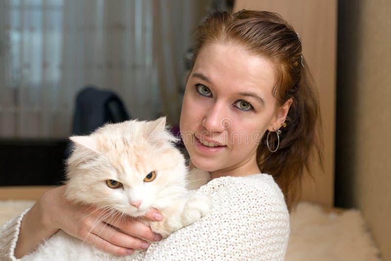 De jonge vrouw speelt met haar kat royalty-vrije stock fotografie