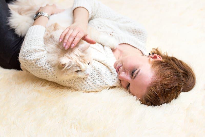 De jonge vrouw speelt met haar kat stock foto's
