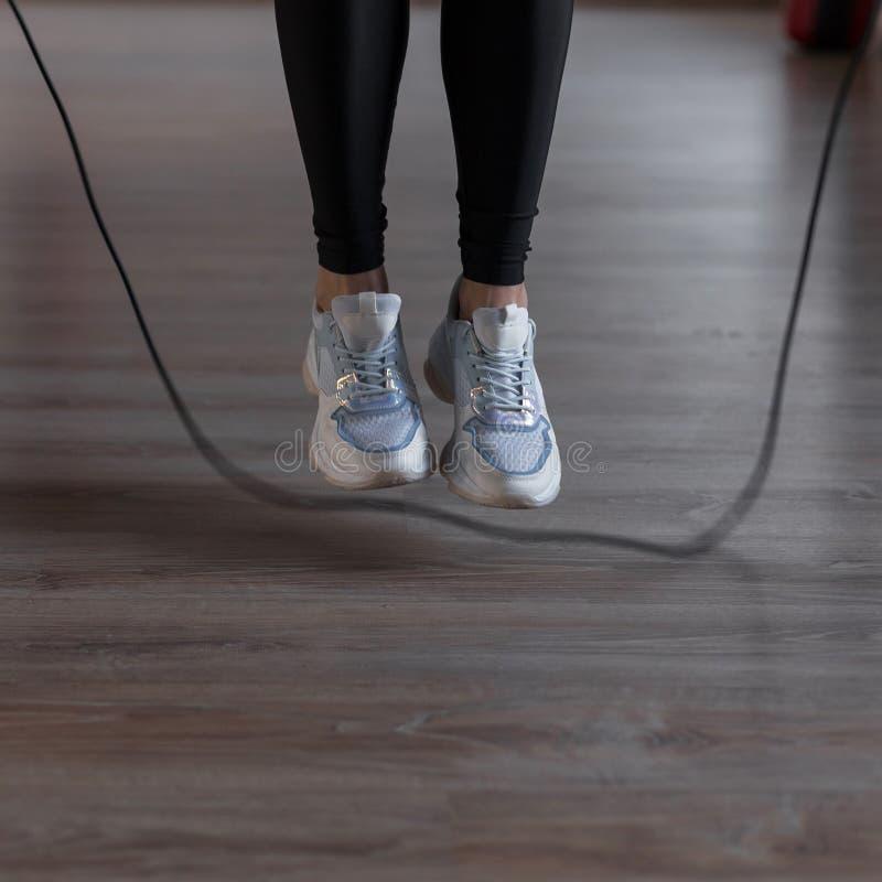 De jonge vrouw in sporten zwarte beenkappen in modieuze tennisschoenen doet touwtjespringen bij de gymnastiek Het meisje gaat bin royalty-vrije stock foto's
