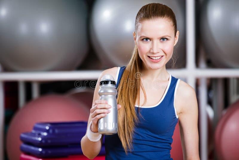 De jonge vrouw in sportkleding houdt een waterfles stock foto
