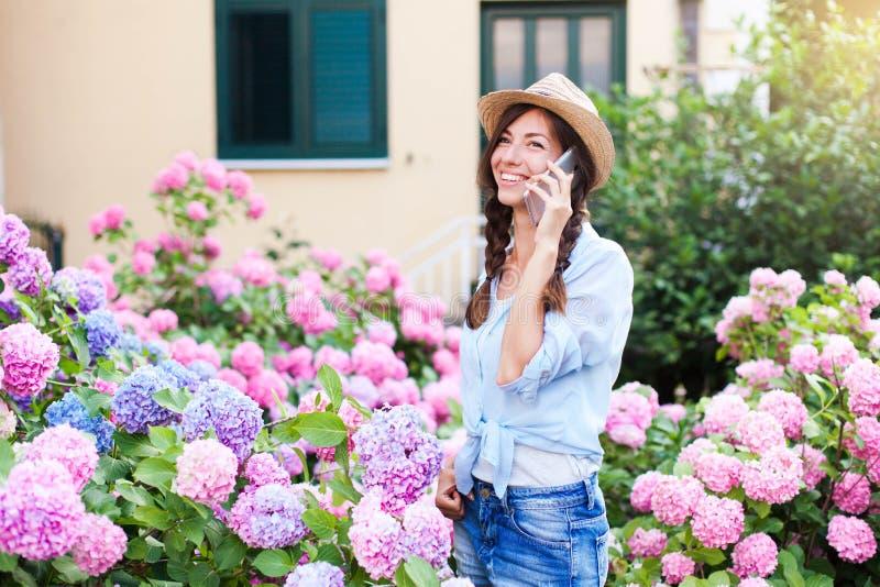 De jonge vrouw spreekt op mobiele telefoon Gelukkig meisje met glimlach in tuin met struiken van hydrangea hortensia royalty-vrije stock afbeeldingen