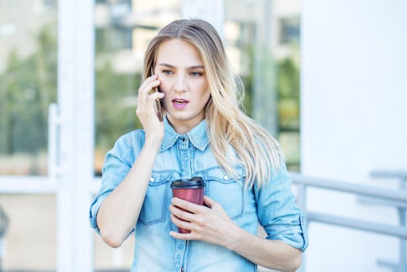 De jonge vrouw spreekt op de telefoon en drinkt koffie Stedelijk concept levensstijl, het werk royalty-vrije stock foto's