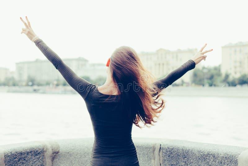 De jonge vrouw status met achter haar hief zijn handen op, en toont overwinningsteken, eens vrij van de stad en het werk Vrijheid royalty-vrije stock fotografie