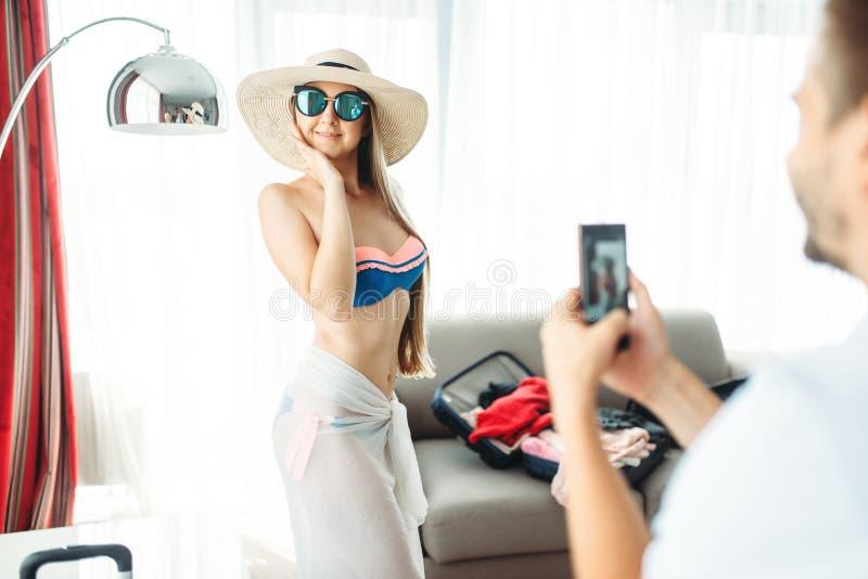 De jonge vrouw stelt in zwempak, prijzen op reis stock afbeeldingen