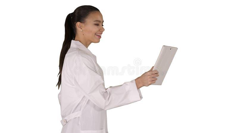 De jonge vrouw tablet van de artsenholding in haar handen en het maken van videogesprek op witte achtergrond royalty-vrije stock afbeeldingen