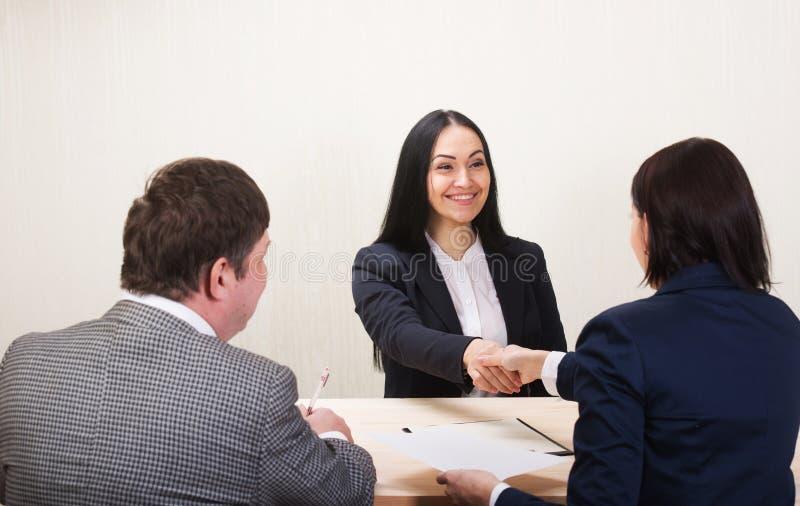 De jonge vrouw tijdens baangesprek en de leden van managemen royalty-vrije stock afbeeldingen