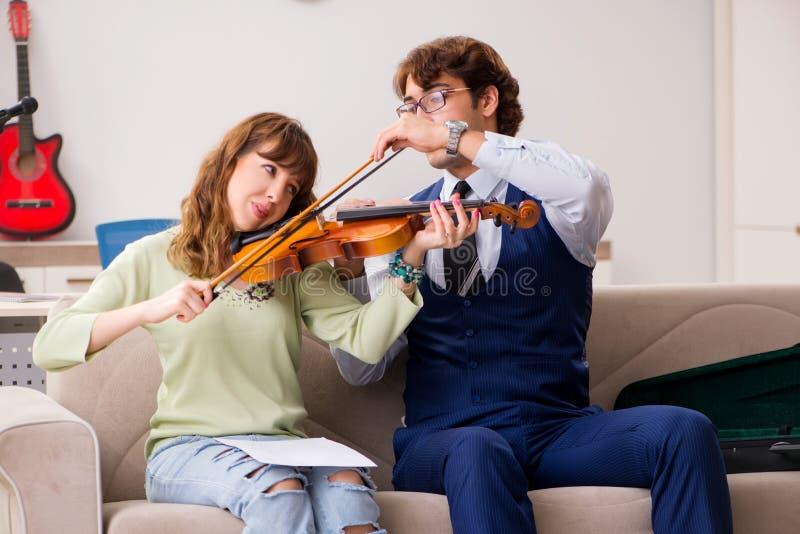 De jonge vrouw tijdens muziekles met mannelijke leraar royalty-vrije stock fotografie