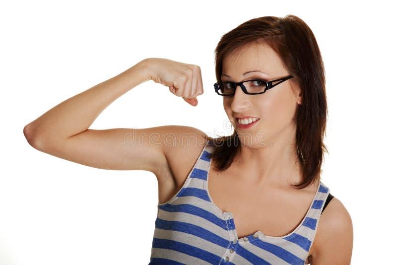 De jonge vrouw toont haar bicepsen. stock foto's