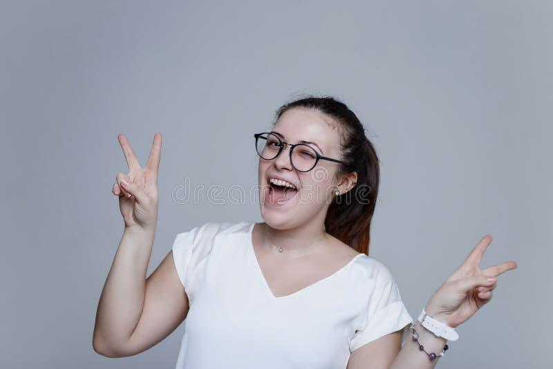 De jonge vrouw toont de handenemoji van het vredesteken stock foto