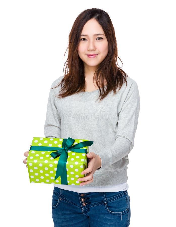 De jonge vrouw toont met giftbox royalty-vrije stock afbeelding
