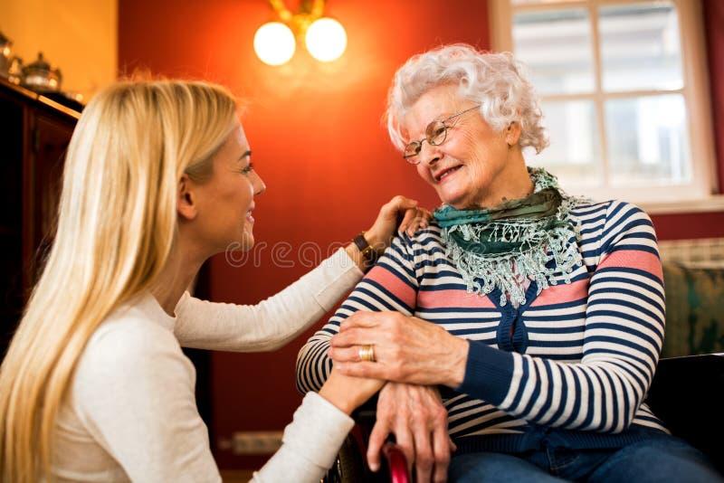 De jonge vrouw troost haar grootmoeder in rolstoel over haar heelt royalty-vrije stock afbeelding