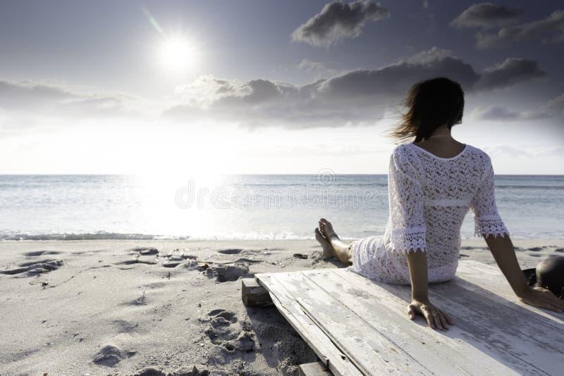 De jonge vrouw van achter zitting door het overzees bekijkt de horizon bij dageraad in de wind, gekleed in een wit kantkleding en royalty-vrije stock foto's