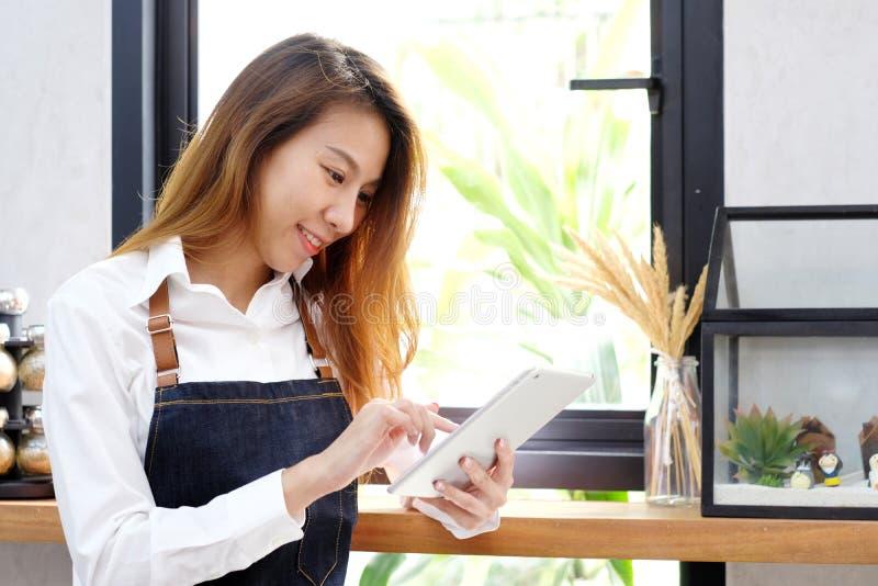 De jonge vrouw van Azië, barista, die tablet gebruiken bij koffie tegenbackgrou stock afbeelding