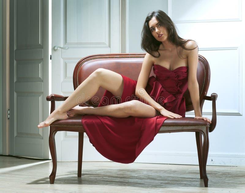 De jonge vrouw van de schoonheid op bank stock afbeeldingen